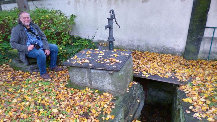 Peter sitzt am Brunnen vor der rückwärtigen Mauer