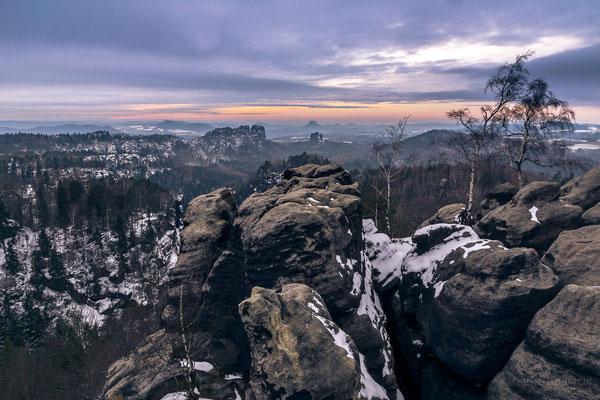 Winterliche Abendstimmung auf dem Carolafelsen mit Blick zu den Schrammsteinen und dem Lilienstein