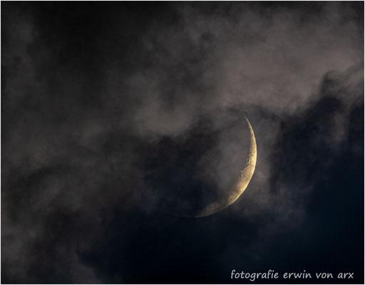 Die Mondsichel zeigt sich zögerlich durch Wolkenlücken