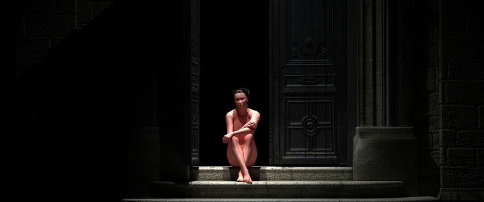 Sitzender weiblicher Akt in altem Toreingang. Kunst von Marcus Löhrer auf der Aachener Kunstroute 2017 in der Galerie Frutti dell Arte. Auch in der Aula Carolina