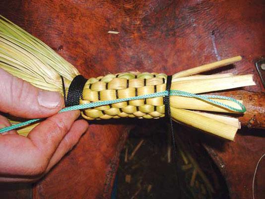 (4) 写真のターコイズ色の紐は道具。肝心の紐の後端を最後の数本の巻きの下にくぐらせて引っ張り、固定させるために使う。