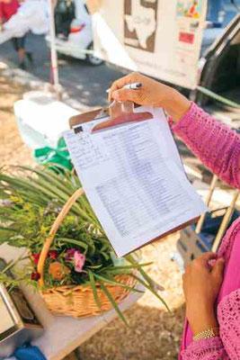会員は朝に作物や卵を持ち込み、販売する品目と数量を用紙に記入。写真は Nitya Uthenpong の食べられる花とニラ。Photo by Scott David Gordon.