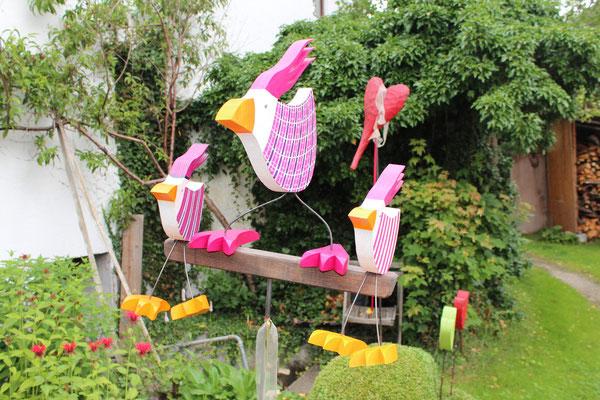drei Vögel auf Balken, groß Mitte stehend breit, zwei Mittlere sitzend