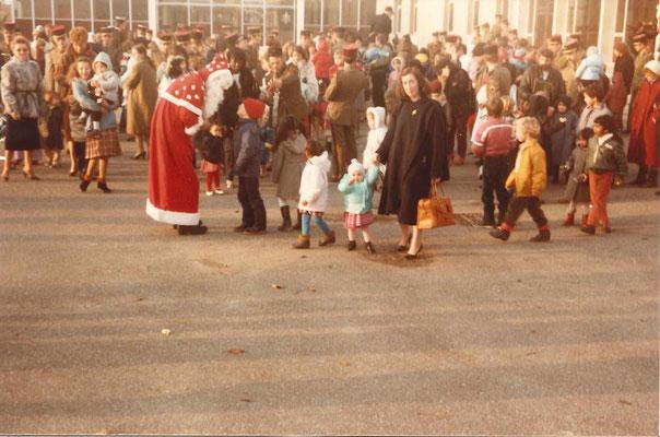 Bain de foule du Père Noël devant le foyer du soldat. Au premier plan, en civil, le LTN CUVELOT et sa fille Caroline.