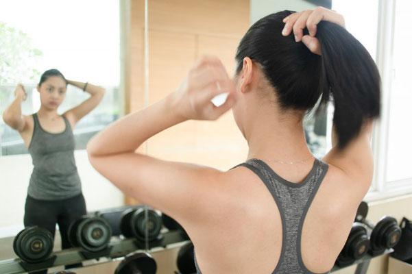トレーニング前に髪を纏める女性