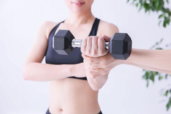 パーソナルジムで腕を鍛える女性