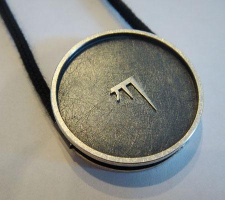 Gent KA  Ø 32 mm • Silber teils geschwärzt • KA erhaben, zwei Ösen, flach mit Zarge • private collection