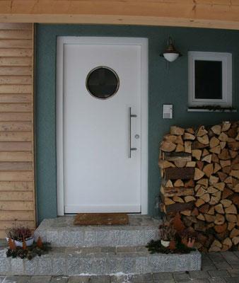 weiße Eingangstür mit Rundfenster