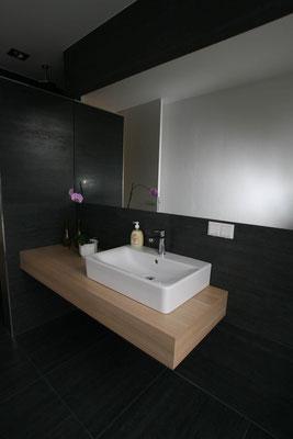 Bad in schwarz mit minimalistischem Waschtisch aus hellem Holz