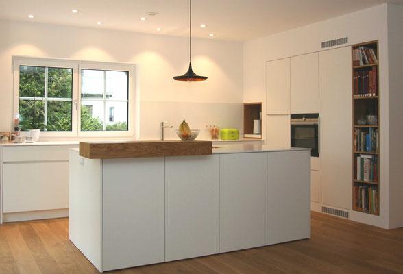 Weiße Küche mit Kochinsel und Bücherregal in Holz