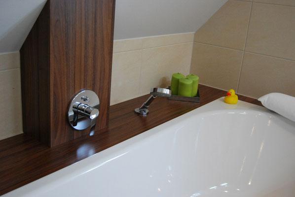 Maßgefertigte Badewanne aus dunklem Holz in Dachschräge