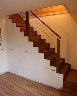 Holztreppe mit weißem Schrank mit Griffen