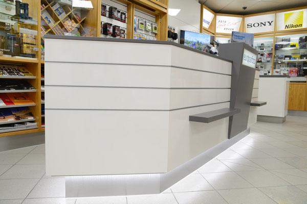 Moderne Laden-Theke in Grau und Weiß mit indirekter Beleuchtung