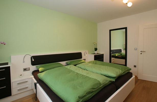 schwarz weißes Doppelbett in grünem Schlafzimmer