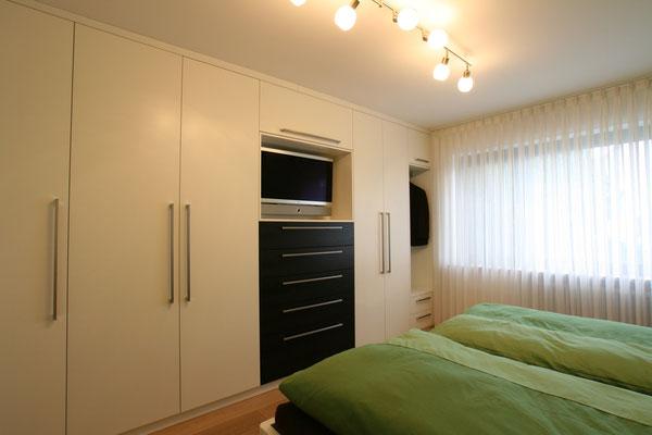 Schlafzimmer Schrankwand in weiß mit schwarzem TV-Board