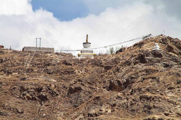 """Ein Berg nahe bei Shigatse. Hier finden - wie meist in Tibet üblich - Luftbestattungen statt. Dabei wird der Leichnam des Verstorbenen nach einer letzten Beschwörung durch einen Lama zerteilt und von den Geiern """"in den Himmel getragen""""."""