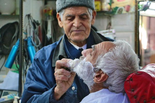 Friseur beim Rasieren eines Kunden in der Medina von Fes.