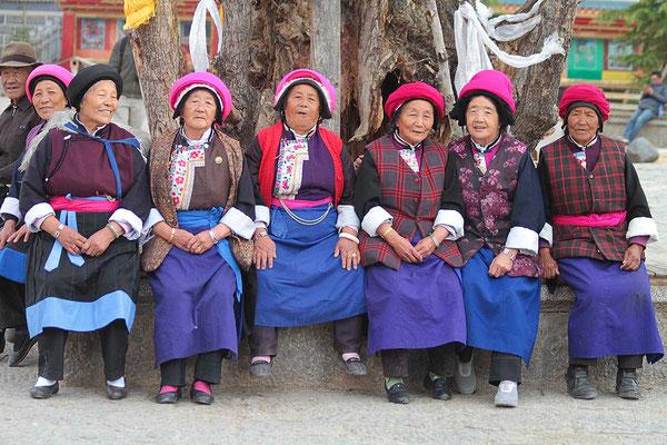 Ältere Frauen in traditioneller Kleidung versammeln sich auf dem zentralen Platz und warten bis der Tanz beginnt.