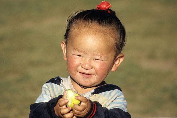 Ein kleiner Junge feut sich über den mitgebrachten Apfel.