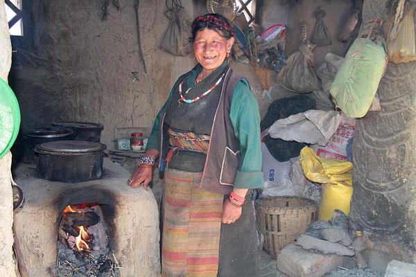 Unterwegs in einem Dorf auf dem Weg von Shigatse nach Gyantse. Bauersfrau an der Kochstelle.
