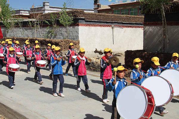 """Unterwegs in einem Dorf auf dem Weg von Shigatse nach Gyantse. Heute ist der """"Tag des Kindes"""", daher der Umzug."""