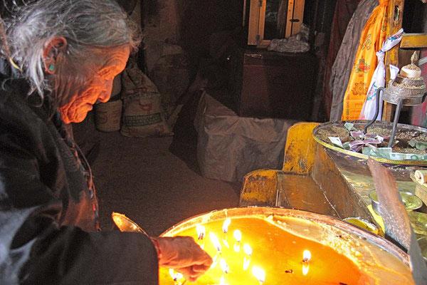 Pilgerin im Pelchor Chode Kloster bei Gyantse. Sie opfert Yakbutter für ihren Buddha.