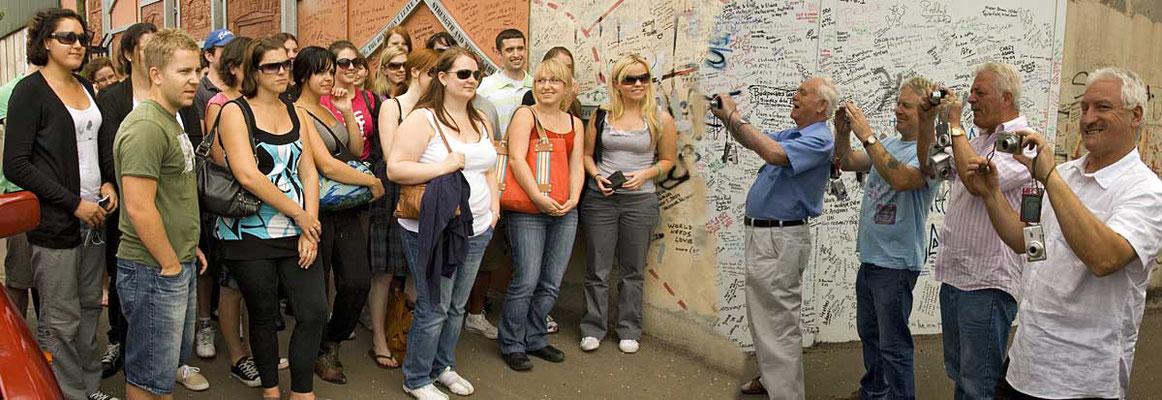 Die Gruppe lässt sich vor der Mauer von den Taxifahrern fotografieren. (Fotomontage)