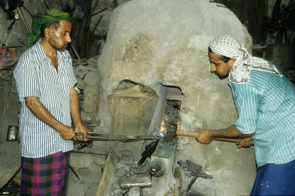 Die Sichelschmiede stehen trotz sengender Hitze vor ihrem Ofen und schmieden den glühenden Stahl.