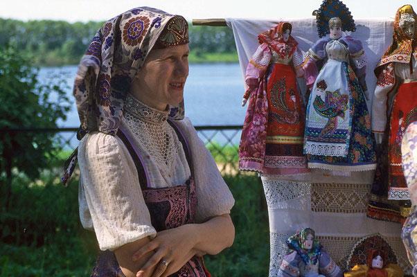 Handarbeiten werden den Touristen gerne als Souvenirs angeboten. Eine junge Frau zeigt sich stolz in ihrer wertvollen Tracht..