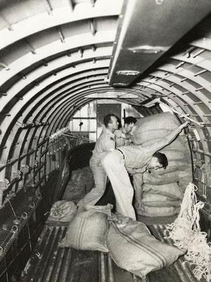 "Kickers! (Usually ground crew) free dropping (without parachutes) Rice near Burmese villages. ""Kickers/Absetzer"" werfen Reissäcke ohne Fallschirm ab nahe Dörfer in Burma"
