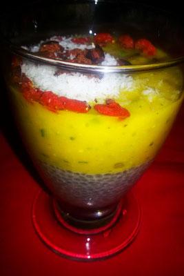 Budino di semi di chia alla vaniglia con smoothie al mango e decorato con farina di cocco, bacche di Goji e fave di cacao