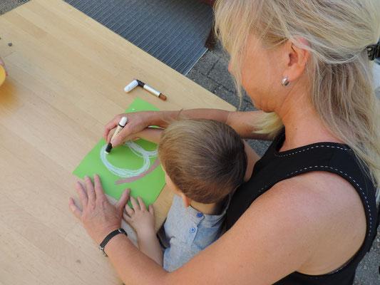Durch Malgeschichten, bei denen wir Erzieherinnen zusammen mit dem Kind nach einem Reim malen, fördern wir die Grafomotorik und Sprache.