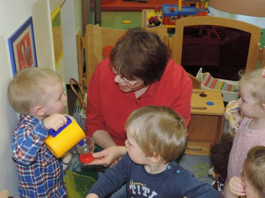 In der Puppenecke fördert die Erzieherin das Zusammenspiel und soziale Verhaltensweisen der Kinder.