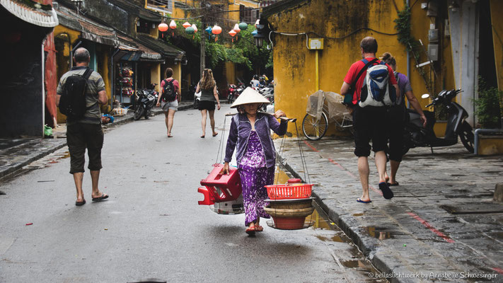 one is walking in the one direction and the others in the other direction in Hoi An
