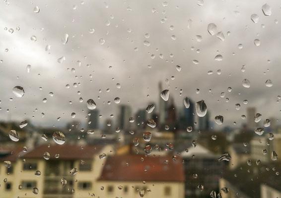 Frankfurter Skyline im Regen durch eine Fensterscheibe fotografiert.