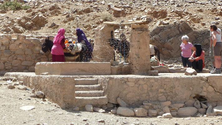 Deux dames viennent chercher de l'eau au puits