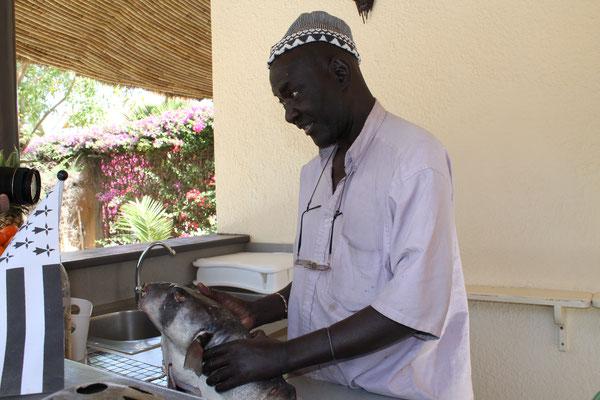 Le pêcheur nous apporte le repas du midi, sous la paillotte il le nettoie! pratique!
