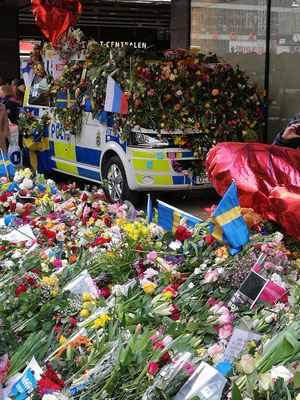 Blumen auf einem Polizeiwagen vor Åhléns City