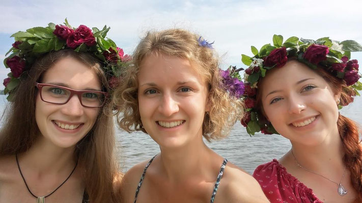 Praktikantinnen mit Blumenkränzen an Midsommar