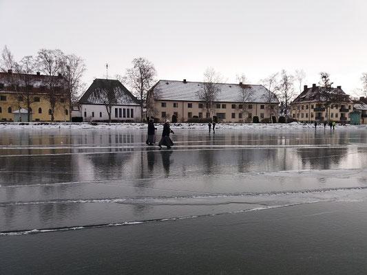 Eislaufen mit zwei Schwestern auf dem Vätternsee vor der Kulisse des Gästeheims mit Kirche und Kloster