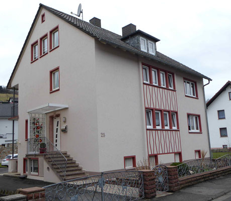 verputztes Haus mit roten Farbelementen an den Fenstern