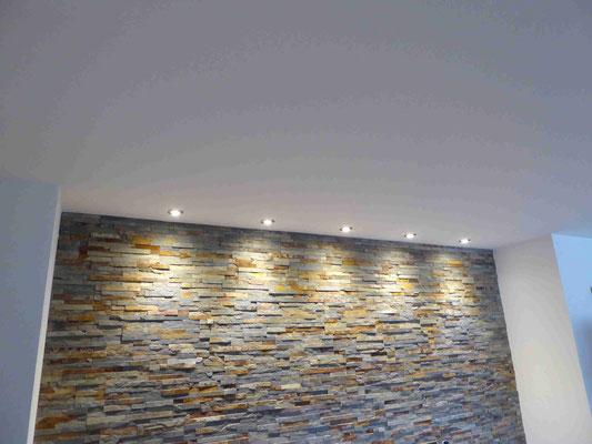 Wand mit Steinwandoptik und eingebauten Strahlern
