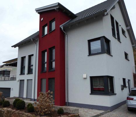 modernes Wohnhaus mit weißem Putz und roten Farbelementen im Eingangsbereich