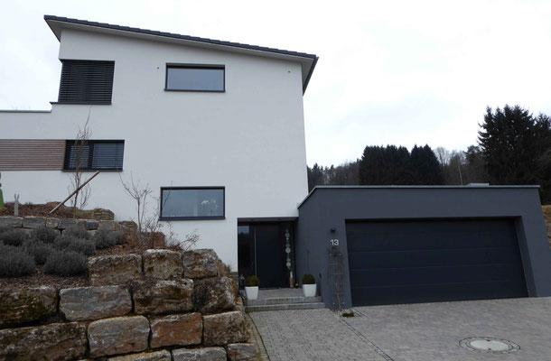 modernes Haus mit weißem Außenputz und grauer Garage