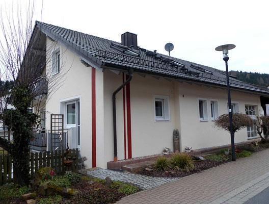 Haus mit beigen Außenputz und roten Farbstreifen