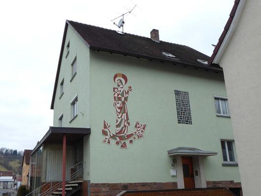 Haus mit mintgrünem Putz und Fassadenmalerei