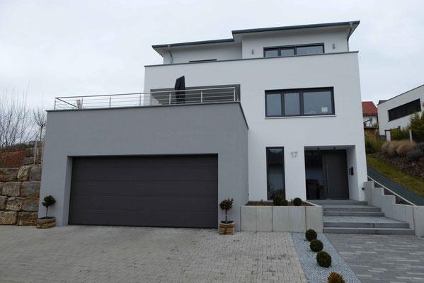 modernes Haus mit weißem Putz und hellgrauer Garage