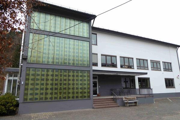 Gewerbe mit weißem Außenputz und grünen Glaselementen im Treppenhaus
