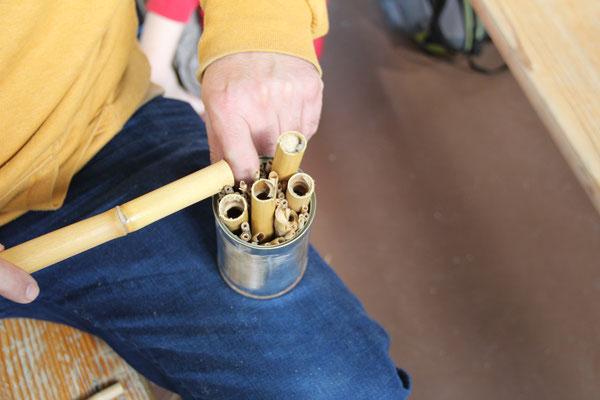Hier wird die leere Dose mit Bambusästen und Schilfrohren gefüllt.