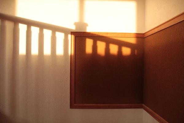 朝日に照らされる土の額縁と階段手摺